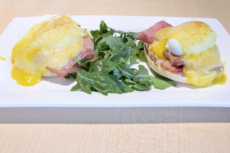 Eggs Benedict with Canadian Bacon Hollandaise Sauce and Organic Green over English Muffins Breakfast Dish photo