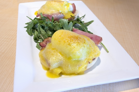Eggs Benedict with Canadian Bacon Poached Eggs Hollandaise Sauce and Organic Green over English Muffins Breakfast Dish Closeup