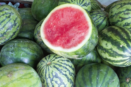 seedless: Watermelons Seedless Whole and Halved at Fruit Stand Closeup Stock Photo