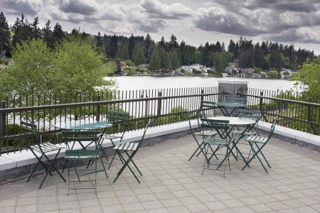 lakefront: Garden Outdoor Patio Seating by the Lake with View of Waterfront Homes Stock Photo