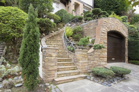 hardscape: Stone Veneer Faccade on Home Exterior with Manicured Front Entrance Yard Landscape Stock Photo