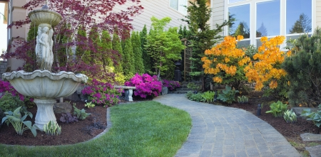mugo: Frontyard Landscaping with Water Fountain and Brick Pavers Path with Azalea Flowers in Bloom Stock Photo