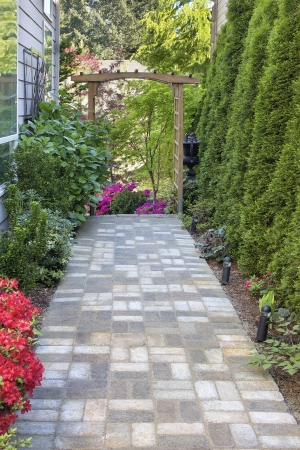 Garden Brick Paver Path Walkway with Wood Arbor Landscape Light Trees and Flowering Plants Stock Photo - 19508657