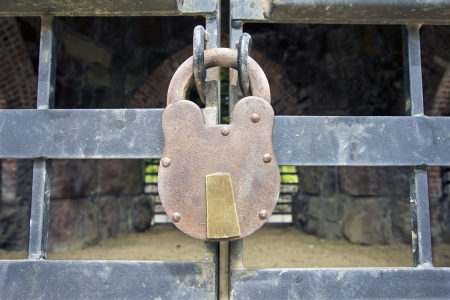 gated: Old Iron Padlock on Gated Historic Building Exterior Stock Photo