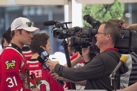 ed: PORTLAND, OREGON, MAY 14 2013: Portland Winterhawks Ice Hockey Team members being interviewed by Television Station at Pioneer Square Rally on May 14, 2013, after winning the Western Hockey League Championship and bringing home the Ed Chynoweth Cup Editorial