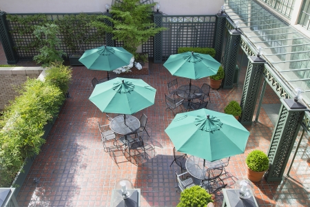 hardscape: Outdoor Patio Seatings with Tables Chairs and Green Umbrellas Stock Photo