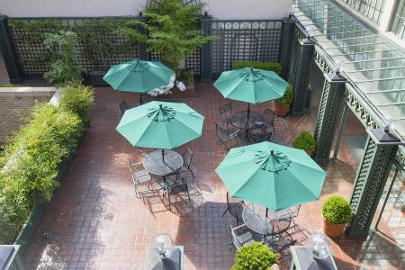 Sitzmöbel mit Außenterrasse Tische Stühle und Regenschirme Grün