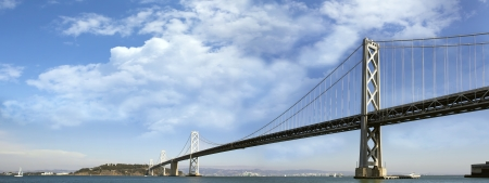 ca: San Francisco Oakland Bay Bridge with White Puffy Clouds on Blue Sky Panorama