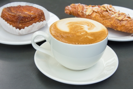 Cup of Caffe Latte with Almond Croissant and Flaky Pastry in Background
