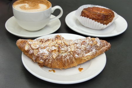 Almond Croissant French Pastry on White Plate with Cup of Latte