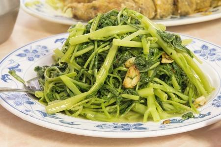 semi aquatic: Stir Fry Chinese Kangkong Green Vegetable with Garlic Dish Closeup Stock Photo