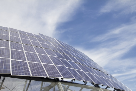 photons: Group of Solar Panel Modules Against Blue Sky with Clouds