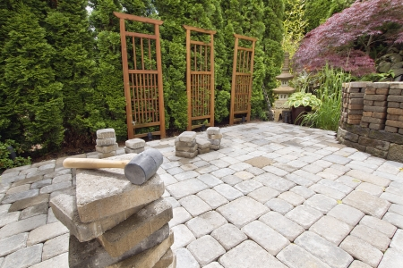 pavers: Stack of Brick Pavers for Hardscape in Backyard Landscaping with Trellis and Trees Stock Photo