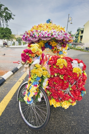 trishaw: Trishaw Decorated with Colorful Silk Flowers Parked on Roadside in the Port Town of Malacca Malaysia