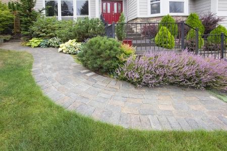 Front Yard Garden Curve Brick Paver Pad met Groen Gras Gazon Bloeiende Planten Bomen en Struiken