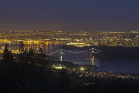 port stanley: Vancouver BC Canada Cityscape with Stanley Park and Lions Gate Bridge Over Burrard Inlet at Evening Blue Hour