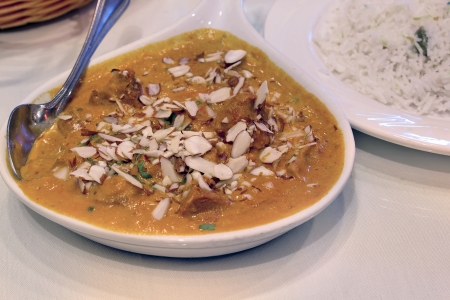 East Indian Food Lamb Curry Korma with Sliced Almonds and Basmati Rice Closeup