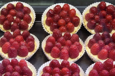 Lemon Curd Fruit Tarts with Raspberries at Bakery Shop photo
