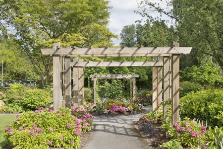mondo: Wood Arbor Over Garden Path with Plants Trees and Flowers Blooming in Summer