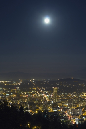 Harvest Full  Moon Rise Over Portland Oregon at Night with City Lights and Traffic Light Trails at Night photo