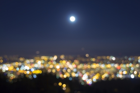 Harvest Full Moon Rise Over Blurred Defocused City Building Lights Landscape at Evening Blue Hour  Stock Photo
