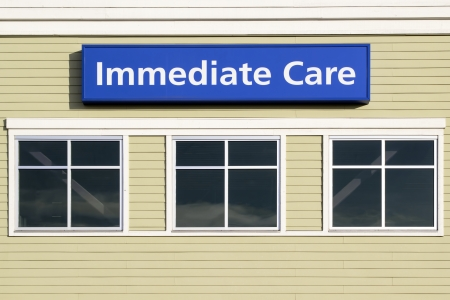 urgent care: Immediate Care Sign Above Windows Outside Hospital or Emergency Clinic Building