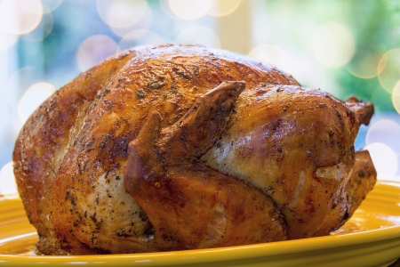 Cooked Roast Turkey on Yellow Platter for Thanksgiving Dinner Closeup with Blurred Bokeh Lights in Background Stock Photo