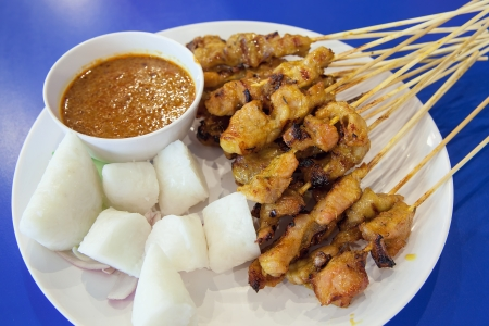 Pork Satay with Penut Sauce Rice Cake Ketupat Onions and Cucumbers Closeup