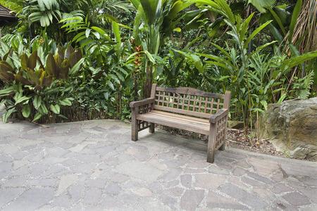 石舗装パティオ付きのトロピカル ガーデンの木製ベンチ