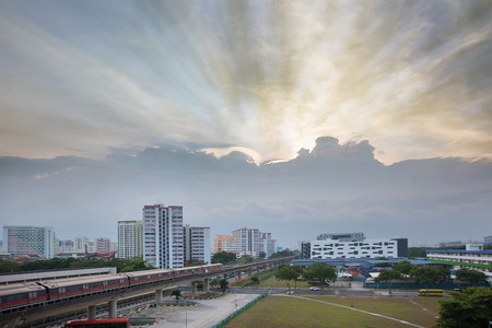 hdb: Sunset with Sun Rays Over Singapore Housing Estate by the MRT Train Track