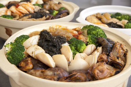 feast: Poon Choi Hong Kong Cantonese Cuisine Big Feast Bowls with Seafood and Vegetables for Chinese New Year Dinner Closeup Stock Photo