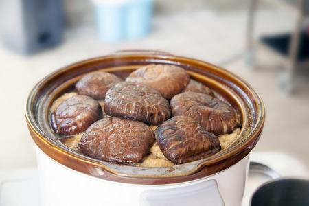 slow cooker: Stewed Shiitake Black Mushrooms Cooking in Slow Cooker Pot Closeup Stock Photo