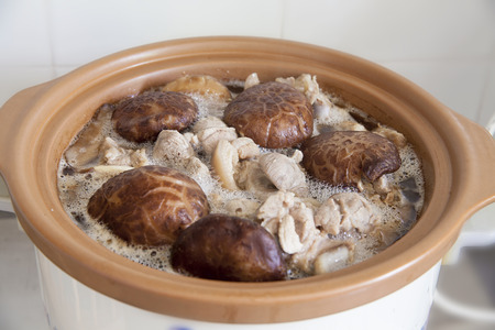 slow cooker: Stewed Shiitake Black Mushrooms and Pork Cooking in Slow Cooker Pot Closeup