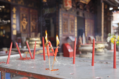 Burning Red Candles as Offerings to Chinese Gods at Chinese Temple in Malacca Malaysia photo