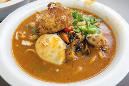 hard boiled: Mee Rebus, Malay Local Noodle Dish with Hard Boiled Egg, Fried Tofu, Cut Chili Peppers and Potato Cake Stock Photo