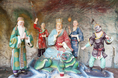 diorama: SINGAPORE - FEBRUARY 1, 2014  Di Zang Wang Ksitigarbha Buddha, in charge of the Tenth Court of Hell, with Attendants Statues Diorama at Haw Par Villa Theme Park