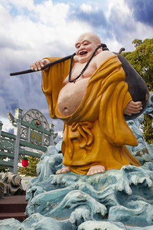 SINGAPORE - FEBRUARY 1, 2014: Ho Tai Laughing Buddha Statue by Gate at Haw Par Villa Theme Park