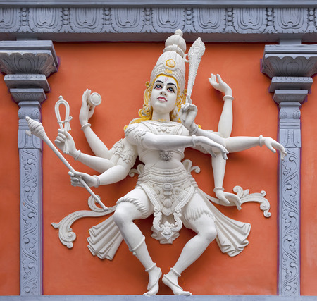 hindu god shiva: Nataraj Dancing Form of Lord Shiva Hindu God Orange and White Statue on Temple Exterior Wall Relief