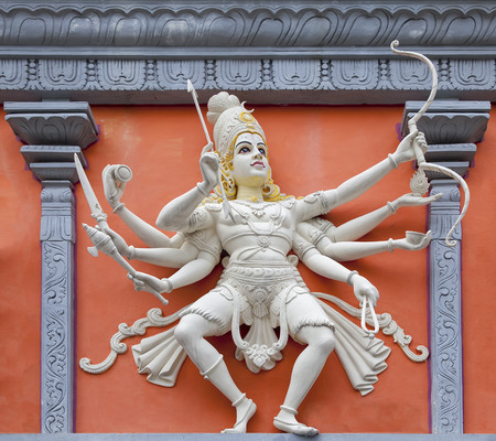 hindu god shiva: Nataraj Dancing Form of Lord Shiva with Bow and Arrow Hindu God Orange and White Statue on Temple Exterior Wall Relief