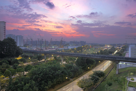 Colorful Sunset Over Punggol Housing Estate with Light Rail Track and Freeway in Singapore photo
