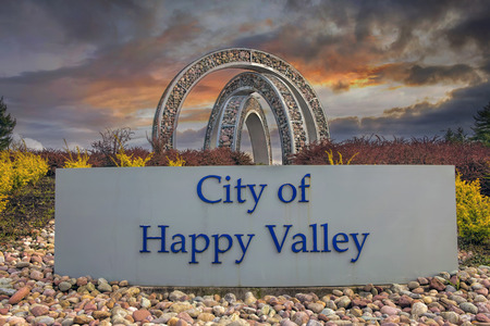 incorporated: HAPPY VALLEY, OREGON - MARCH 30, 2014: City of Happy Valley Sign with Steel and Stone Art Sculpture at Entrance to th city. Happy Valley is in Clackamas County  Oregon and Incorporated in 1965. Editorial