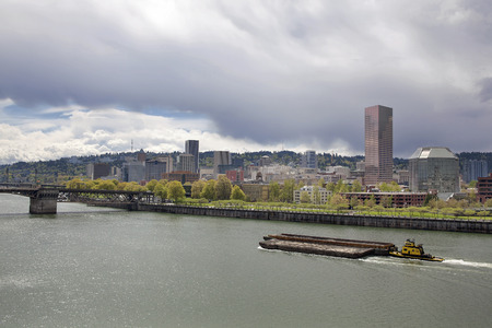 oldtown: Tugboat Pushing Barge Along Willamette River with Portland Oregon City Skyline Stock Photo