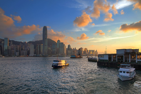 Hong Kong Island Central City Skyline from Kowloon Ferry Pier Along Victoria Harbor Sunset photo