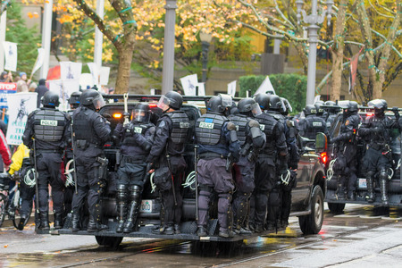 occupy wall street: PORTLAND, OREGON - NOVEMBER 17, 2011: Police in Riot Gears on Vehicles in Downtown Portland, Oregon during a Occupy Portland Protest Against Banks on the first anniversary of Occupy Wall Street