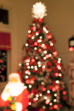 topper: Christmas Tree Decorated with Lights Candy Cane Ornaments Tree Topper and Santa Claus Statue Blurred Defocused Bokeh Background