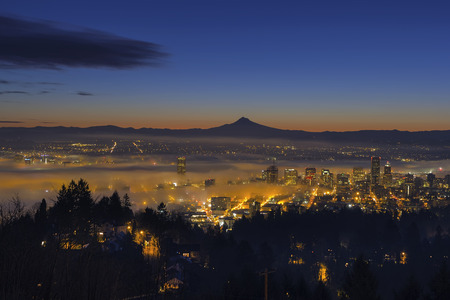 mt  hood: Thick Fog Rolling at Dawn over cityscape of downtown Portland Oregon with city lights and silhouette of Mt Hood Stock Photo