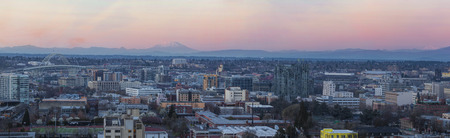 alpenglow: View of Portland Oregon Pearl District Cityscape with Mt St Helens and Mt Adams Fremont Bridge during Sunset Panorama