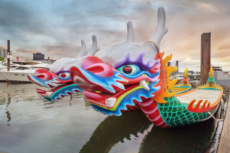 PORTLAND OREGON  May 25 2015: Chinese Dragon Boats docked at Willamette River in Downtown Portland Oregon at Sunset. These Dragon Boats are used for the Portland Rose Festival Dragon Boat Race. It has been a Chinese tradition in Portland for 26 years.