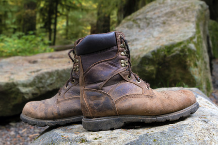 worn out: Worn Out Pair of Hiking Boots Sitting on Top of Rock Along Hiking Trails in Forest