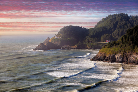mist: Heceta Head Lighthouse on the cliff of Devil's Elbow State Park State Scenic Viewpoint at Sunset Stock Photo